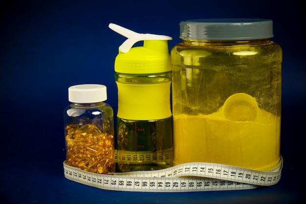 Des protéines dans un pot jaune, un shaker en plastique, des haltères verts et un pot oméga 3