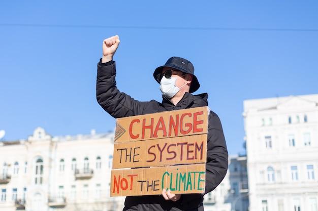 Protestation de piquet en solo sur la place de la ville sauver la planète concept avec slogan changer le système pas le climat