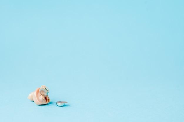 Prothèse auditive sur fond bleu. concept médical, pharmacie et soins de santé.