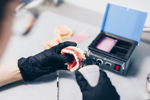 Prothèse dentaire. gros plan des mains tout en travaillant sur la prothèse. mise au point sélective.