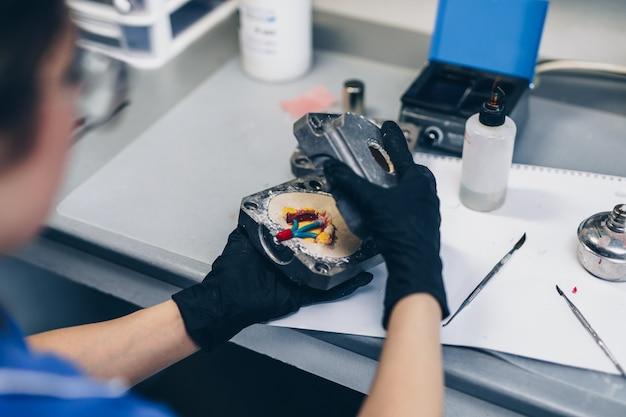 Prothèse dentaire, mains féminines travaillant sur la prothèse. mise au point sélective.