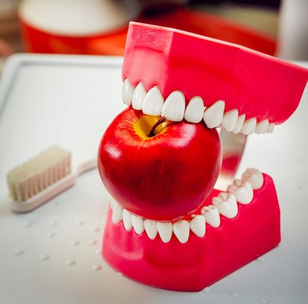 Prothèses mordant une pomme.