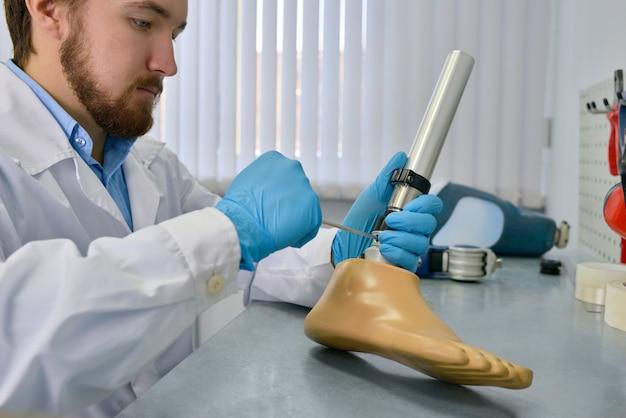 Prothésiste réparant une jambe artificielle