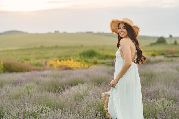 Provence femme détente dans le champ de lavande. dame au chapeau de paille. fille avec sac.
