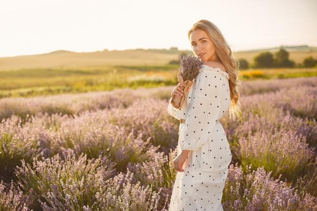 Provence femme détente dans le champ de lavande. dame en robe blanche. fille avec bouquete de fleurs.