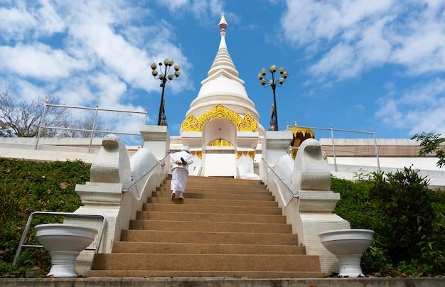 Province de chiang rai, chiang saen, thaïlande-février 9,2021: une religieuse monte les escaliers du feu à la pagode blanche.
