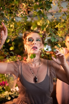 Proximité de la nature. agréable femme rêveuse debout près de l'arbre tout en touchant ses branches