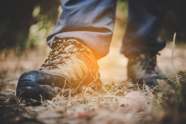 À proximité des pieds de l'homme de l'aventure, marchez sur un sentier de montagne.