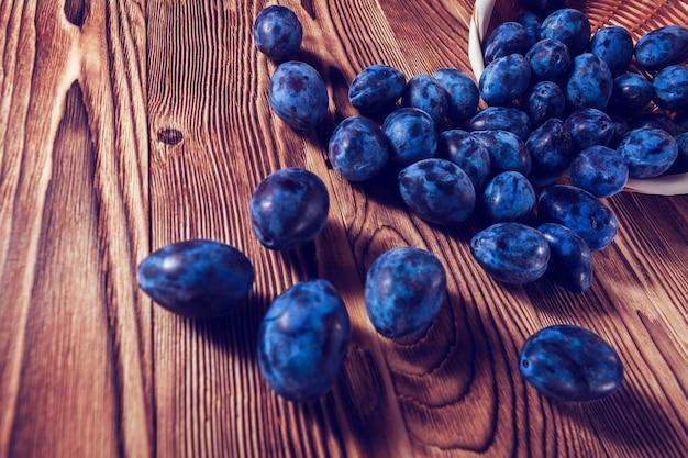 Prune bleue renversée sur un fond en bois