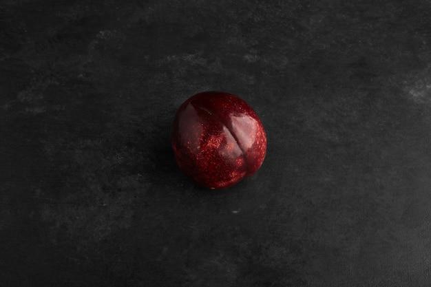 Une prune rouge isolée sur fond noir.
