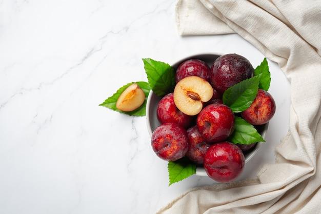 Prune rouge mis dans un bol blanc sur sol blanc