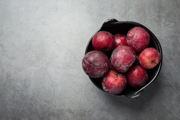 Prune rouge mis dans un bol noir sur sol sombre