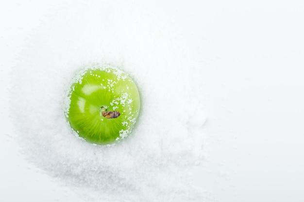 Prune verte avec des cristaux de sel vue de dessus sur un mur blanc