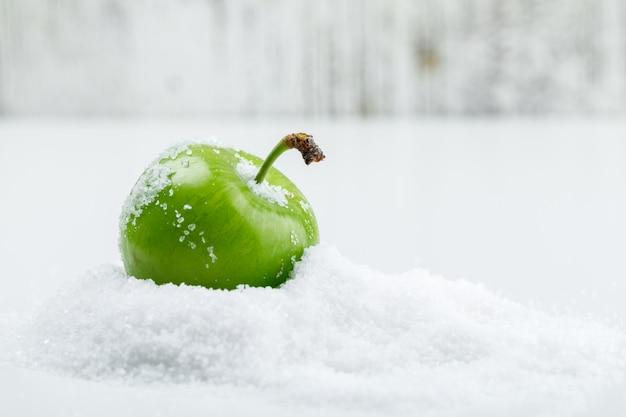 Prune verte salée sur mur blanc et grungy. vue de côté.