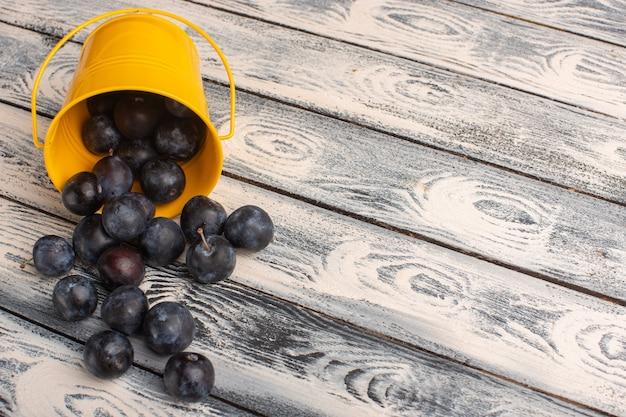 Prunellier mûres fraîches à l'intérieur et à l'extérieur des paniers jaunes sur fond gris
