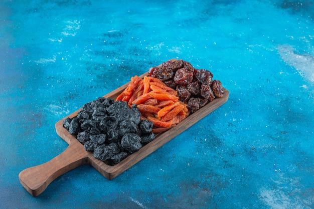 Prunes et abricots séchés sur une planche , sur la table bleue.