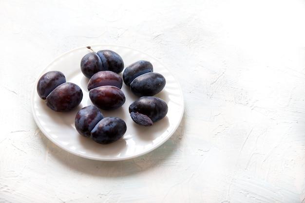 Les prunes d'accrète drôles laides se trouvent sur une assiette en porcelaine blanche. concept de cuisine végétarienne. copiez l'espace.
