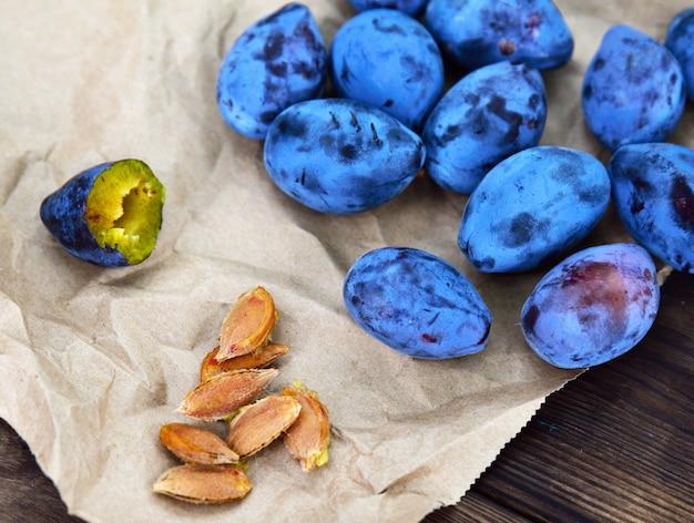 Prunes bleues mûres et os sur papier brun