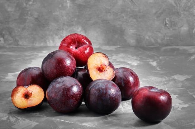 Les prunes bleues mûres se trouvent sur un fond de pierre de béton