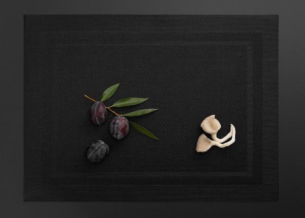 Prunes et champignons sur un drap noir
