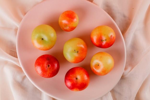 Prunes dans une assiette rose sur une surface textile