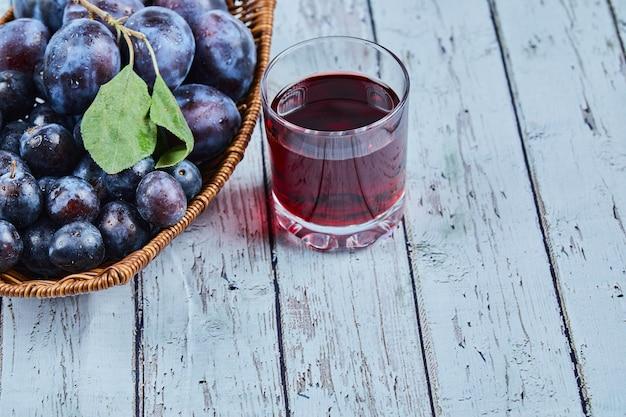 Prunes dans un panier sur bleu avec un verre de jus.