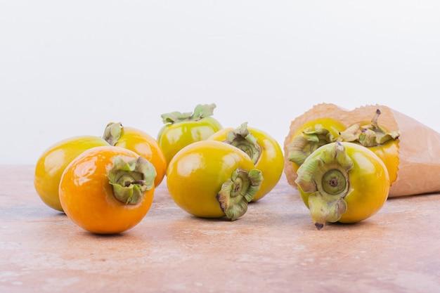 Prunes de dattes jaunes isolés sur une surface rose