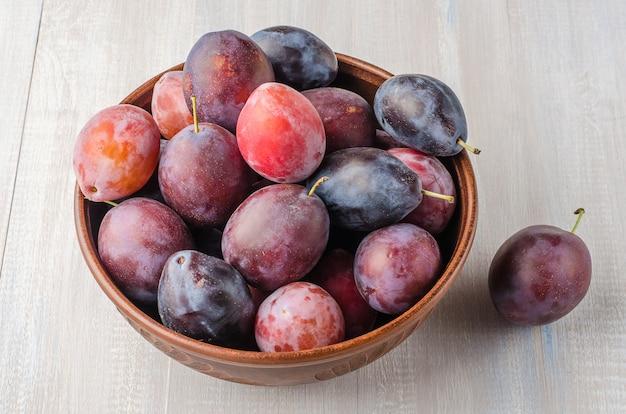 Prunes de différentes variétés sur un fond en bois clair.