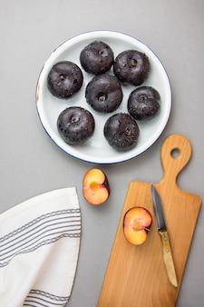 Prunes entières et coupées en deux, pourpre foncé, à chair jaune vif, rougeâtre