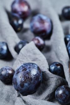 Prunes éparpillées sur nappe grise