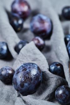 Prunes éparses sur nappe grise.
