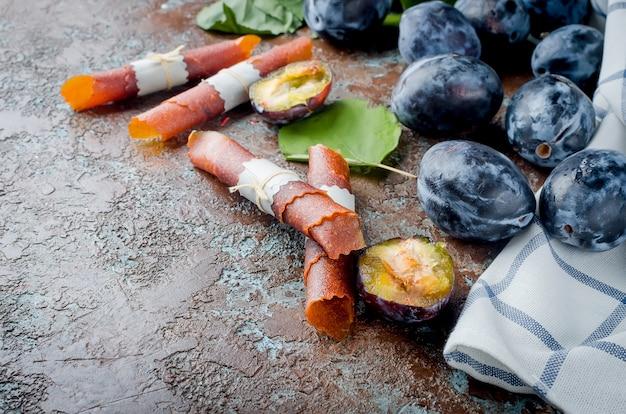Prunes fraîchement cueillies sur la table et pastille de prunes sur une surface sombre