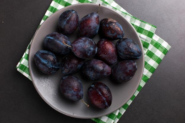 Prunes fraîches et appétissantes dans un bol gris, été, fond.