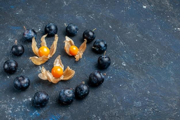 Prunes fraîches bordées en cercle sur un bureau sombre