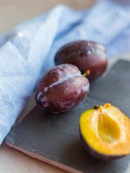 Prunes fraîches avec un chiffon bleu sur fond de table gris. récolte d'automne.