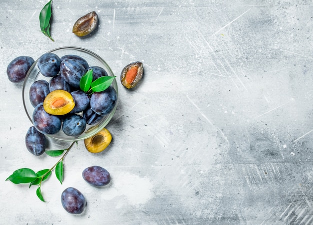 Prunes fraîches dans un bol en verre. sur table rustique blanche