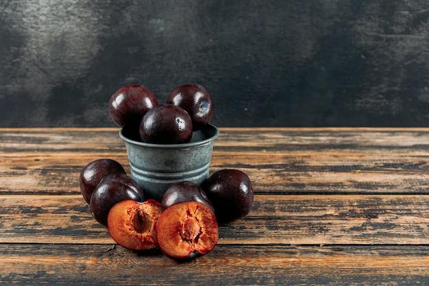 Prunes fraîches dans un petit pot sur un fond en bois foncé et gris foncé. vue de côté.