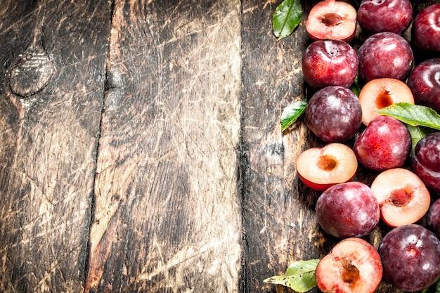 Prunes fraîches et mûres avec des feuilles. sur un fond en bois.