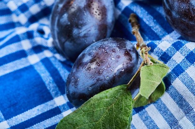 Prunes fraîches sur nappe bleue.