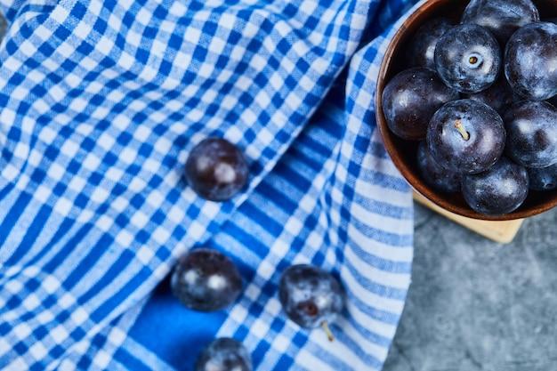 Prunes de jardin sur bol sur marbre avec nappe.