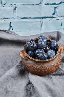 Prunes de jardin sur bol sur nappe grise.