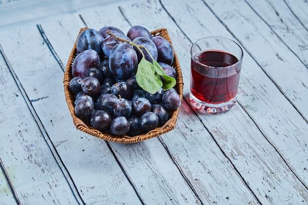 Prunes de jardin dans un panier sur bleu avec un verre de jus.