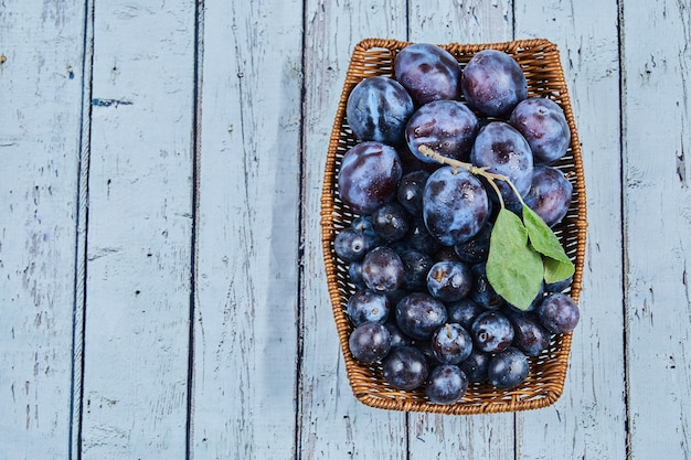 Prunes de jardin dans un panier sur fond bleu. photo de haute qualité