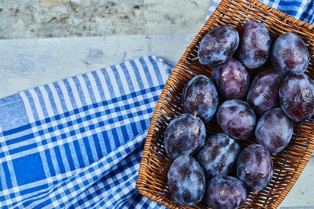 Prunes de jardin sur panier sur table en pierre avec nappe.