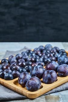Prunes de jardin sur plateau en bois et sur fond sombre. photo de haute qualité