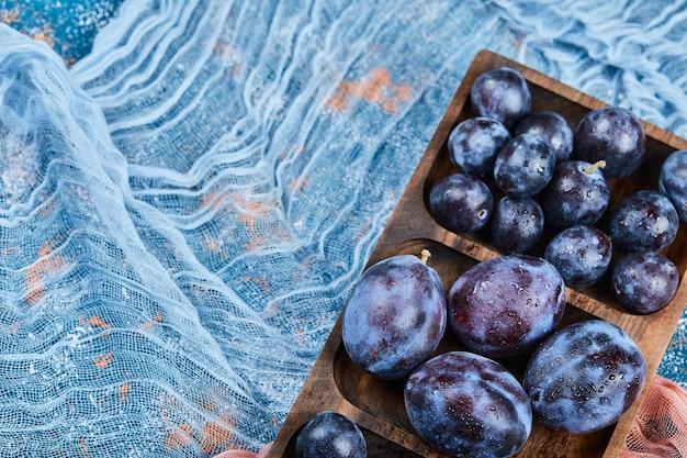 Prunes de jardin sur plateau en bois avec nappe.