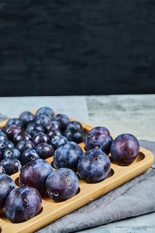 Prunes de jardin sur plateau en bois et sur noir.