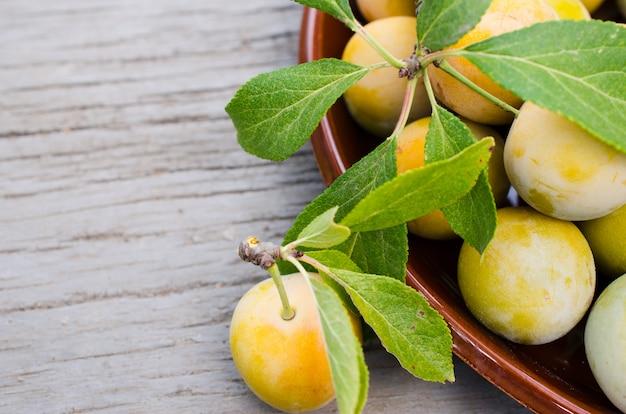 Prunes jaunes cultivées de manière écologique dans un bol.