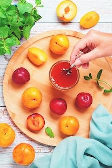 Prunes jaunes et rouges dans une assiette et un pot de confiture de prunes sur une table en bois bleue à plat, concept de conserves de fruits d'automne, espace de copie