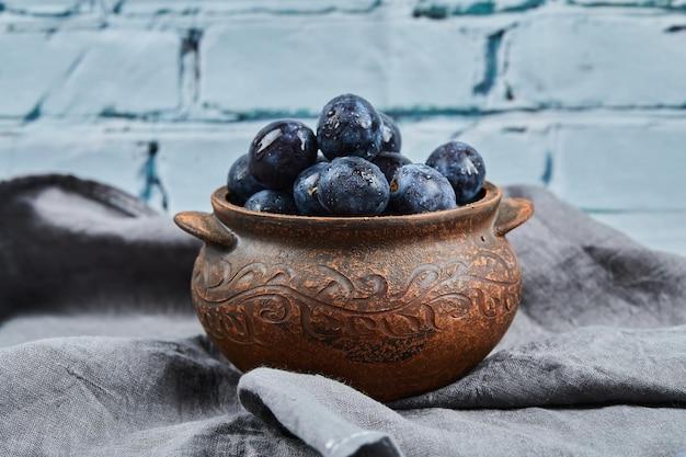 Prunes mûres sur bol sur nappe grise.